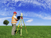 Land surveyor with equipment on green field. The picture was made from three big photos and downsized for better quality.